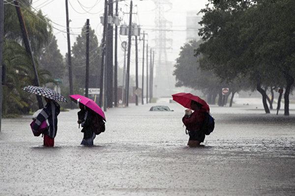 哈維颶風襲擊德州,休斯頓遭遇前所未有的洪災。圖為2017年8月28日,德州休斯頓,水患嚴重,民眾涉水撤離災區。(Erich Schlegel/Getty Images)