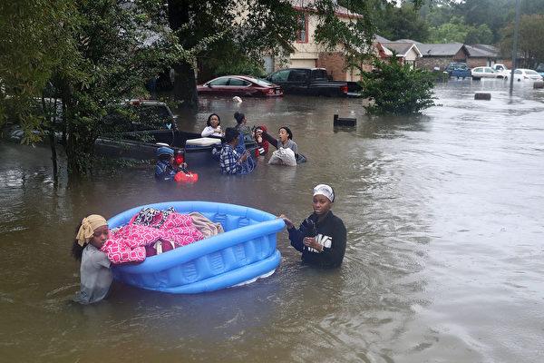 哈維颶風襲擊德州,休斯頓遭遇前所未有的洪災。圖為2017年8月28日,德州休斯頓,水患嚴重,民眾正在撤離災區。(Joe Raedle/Getty Images)