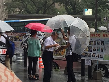 日本法轮功学员8月15日,在东京九段下车站摆真相看板,向人民讲真相,并征集联署举报江泽民的签名,尽管当天遇到大雨,依然有上千名的日本民众和外国游客在联署举报书上签了名。(英杰/大纪元)