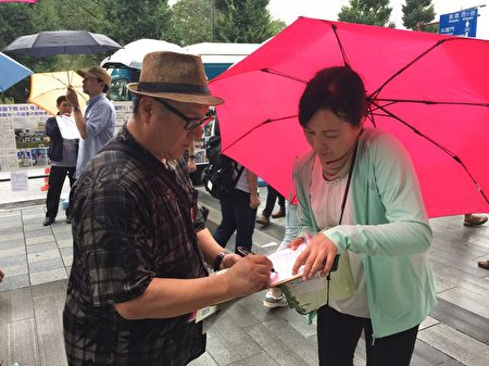 日本法轮功学员8月15日,在东京九段下车站摆真相看板,向人民讲真相,并征集联署举报江泽民的签名,尽管当天遇到倾盆大雨,依然有上千名的日本民众和外国游客在联署举报书上签了名。(英杰/大纪元)