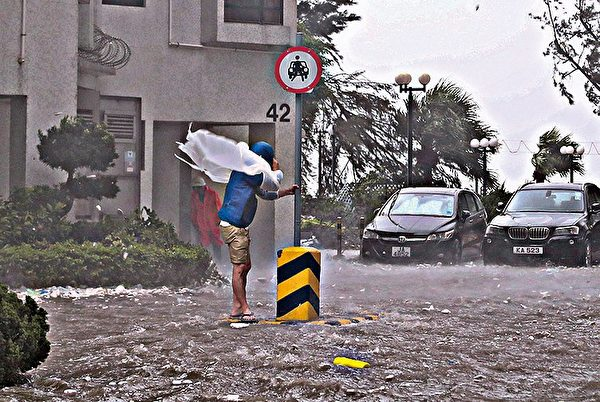 现场所见,杏花邨内马路变成一条河流,水深一度及膝。市民要扶著电线杆等才能站立,否则都被风吹倒。(余钢/大纪元)