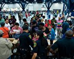 哈維颶風對德克薩斯州休斯頓造成嚴重洪災。圖為8月28日,災民在喬治·布朗會議中心的收容所領取食物。(BRENDAN SMIALOWSKI/AFP/Getty Images)