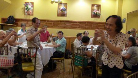 人瑞中心18日在华埠皇上皇酒家办义工感恩餐会。图右为伍宝玲主任,左站立者为中心80多岁的义工兼乒乓健将。