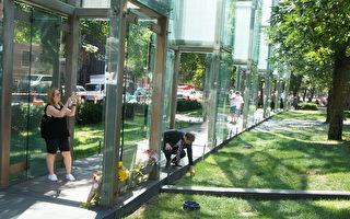 民眾在被砸的大屠殺紀念碑前獻花、拍照。一位男士蹲下身撿拾地上的碎玻璃片。(黃劍宇/大紀元)