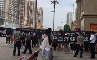 8月26日、27日,湖北荊門市星球商業中心賣女裝的百餘名商戶打橫幅維權遭保安、警察鎮壓。(受訪者提供)
