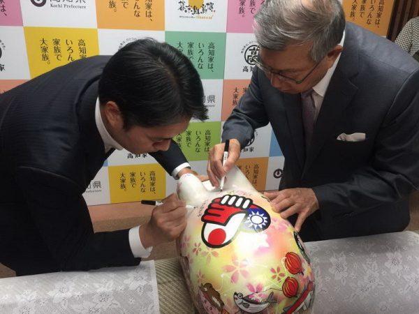 邱镜淳致赠印有台日友好图腾的彩绘神猪,给高知县知事尾崎正直。(新竹县政府提供)