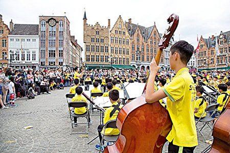英華小學高級管樂團在比利時的布呂赫舊城中心(Bruges)公開表演。(圖片英華小學提供)