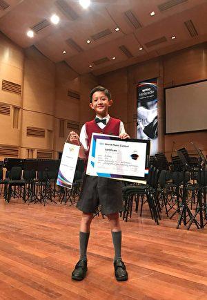 評判發現李泓志同學吹奏巴松管特別出色,特別頒給他最佳巴松管獨奏。這個世界大賽是不設個人獎項的,而且在接近100人的樂團中發現吹巴松管吹得特別出色,還要在台上點名稱讚並頒獎表揚,確是第一次。(圖片英華小學提供)