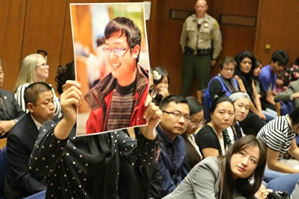 2017年8月16日,紀欣然小姨在庭審現場手舉紀欣然生前照片。(大紀元)