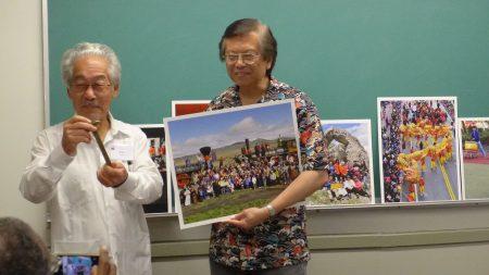 紐約華裔攝影師李揚國與多倫多客家會議發起人羅金生(Keith Lowe,左)在會上,李揚國介紹他與一些華人,在橫跨鐵路建成145周年之際,號召了200名華人和其他亞裔,在複製的火車機車前面合影,彌補當年鐵路完工慶祝活動照片看不到華工身影的缺憾,他們還步行到數英里外的中國拱門。