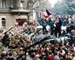 1968年8月21日,布拉格民眾將以蘇聯主導的「華沙條約」國軍隊的坦克團團圍住,捷克青年手持捷克斯洛伐克旗幟站在推翻的卡車上。這次試圖改革社會主義的「布拉格之春」運動遭到鎮壓。(LIBOR HAJSKY / AFP / Getty Images)