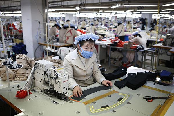 路透社引述丹东的贸易商和企业说,中国纺织品公司越来越多的雇佣朝鲜工厂生产衣服,以利用边境另一边便宜的劳工。这些在朝鲜生产的衣服被贴上中国制造的标签,并出口到全世界。  (Kim Hong-Ji/AFP/Getty Images)