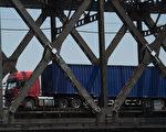 在史无前例的对朝行动当中,中共周一(8月14日)发布命令,执行联合国的最新制裁。图为中朝边境友谊桥,货运车来往两国。( NICOLAS ASFOURI/AFP/Getty Images)