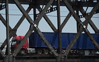 在史無前例的對朝行動當中,中共週一(8月14日)發布命令,執行聯合國的最新制裁。圖為中朝邊境友誼橋,貨運車來往兩國。( NICOLAS ASFOURI/AFP/Getty Images)