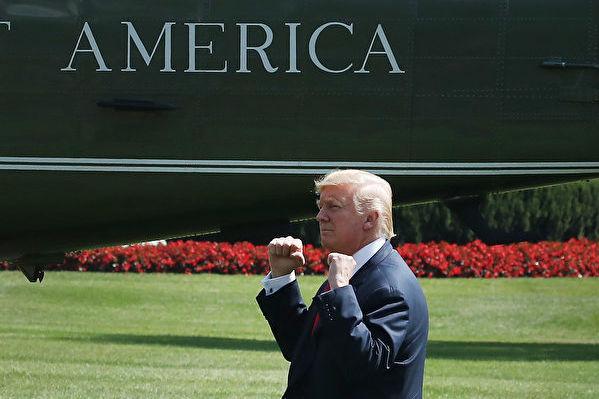 2017年8月4日川普在白宮準備登機飛往新澤西度假,他向圍觀他的民眾做手勢致意。(Mark Wilson/Getty Images)