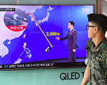 "TOPSHOT - A South Korean soldier walks past a television screen showing a graphic of the distance between North Korea and Guam at a railway station in Seoul on August 9, 2017. President Donald Trump issued an apocalyptic warning to North Korea on Tuesday, saying it faces ""fire and fury"" over its missile program, after US media reported Pyongyang has successfully miniaturized a nuclear warhead. / AFP PHOTO / JUNG Yeon-Je        (Photo credit should read JUNG YEON-JE/AFP/Getty Images)"