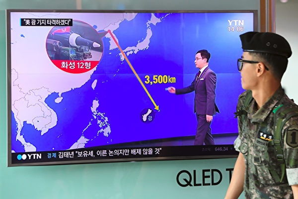 """TOPSHOT - A South Korean soldier walks past a television screen showing a graphic of the distance between North Korea and Guam at a railway station in Seoul on August 9, 2017. President Donald Trump issued an apocalyptic warning to North Korea on Tuesday, saying it faces """"fire and fury"""" over its missile program, after US media reported Pyongyang has successfully miniaturized a nuclear warhead. / AFP PHOTO / JUNG Yeon-Je        (Photo credit should read JUNG YEON-JE/AFP/Getty Images)"""