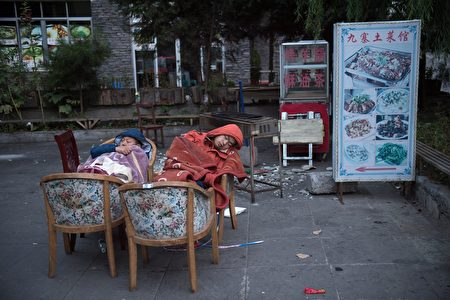 TOPSHOT - Residents fearing aftershocks sleep outside of their homes after an earthquake in Zhangzha in southwest China's Sichuan province on August 10, 2017. The 6.5-magnitude earthquake struck Sichuan province late on August 8, tearing cracks in mountain highways, triggering landslides, damaging buildings and sending panicked residents and tourists fleeing into the open. / AFP PHOTO / Nicolas ASFOURI (Photo credit should read NICOLAS ASFOURI/AFP/Getty Images)