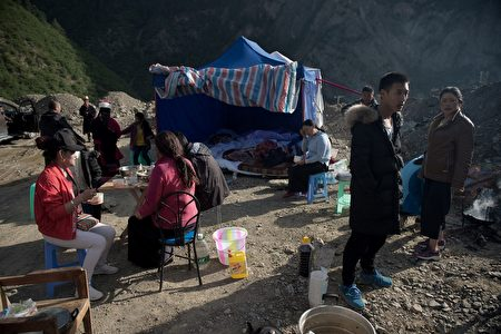 Residents gather on a hill, where they had set up a temporary camp as they feared aftershocks after an earthquake, in Zhangzha in southwest China's Sichuan province on August 10, 2017. The 6.5-magnitude earthquake struck Sichuan province late on August 8, tearing cracks in mountain highways, triggering landslides, damaging buildings and sending panicked residents and tourists fleeing into the open. / AFP PHOTO / Nicolas ASFOURI (Photo credit should read NICOLAS ASFOURI/AFP/Getty Images)