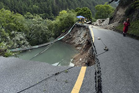 A rescuer walks past a damaged section of road in Jiuzhaigou, two days after a 6.5-magnitude earthquake hit southwest China's Sichuan province, on August 10, 2017. China on August 10 ramped up its response to an earthquake that killed 20 people and injured hundreds, sending supplies and personnel into the mountainous zone as rescuers fanned out to search for more victims. / AFP PHOTO / STR / China OUT (Photo credit should read STR/AFP/Getty Images)