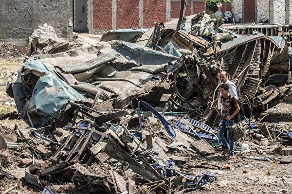8月12日,一老一少兩名埃及人到11日的火車相撞現場搜尋。(KHALED DESOUKI/AFP/Getty Images)