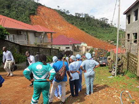 塞拉利昂首都發生嚴重的泥石流,救援人員在災難現場仔細搜尋是否有生還者。 ( SAIDU BAH/AFP/Getty Images)