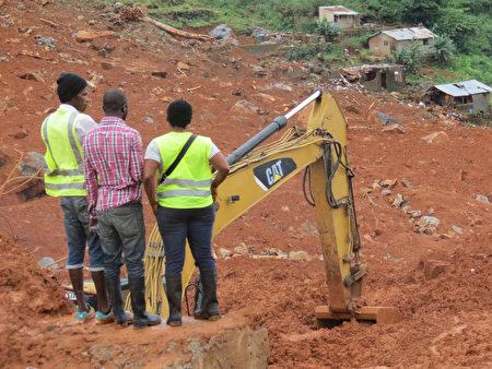 塞拉利昂首都發生嚴重的泥石流,救援人員在災難現場仔細搜尋是否有生還者。(AIDU BAH / AFP / Getty Images)