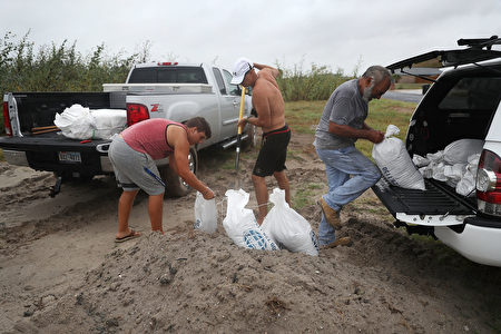CORPUS CHRISTI, TX - AUGUST 25: Cody Munds, Lee Martin and John Pezzi (L-R) fill sandbags as people prepare for approaching Hurricane Harvey on August 25, 2017 in Corpus Christi, Texas. Hurricane Harvey has intensified into a hurricane and is aiming for the Texas coast with the potential for up to 3 feet of rain and 125 mph winds. (Photo by Joe Raedle/Getty Images)