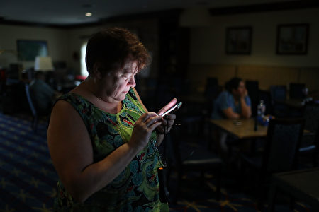 CORPUS CHRISTI, TX - AUGUST 25: Amy Currin watches the weather news on her cell phone after the power went out at the TownePlace Suites hotel where she was taking shelter from Hurricane Harvey at a place she felt was safer than her home on August 25, 2017 in Corpus Christi, Texas. Hurricane Harvey has intensified into a hurricane and is aiming for the Texas coast with the potential for up to 3 feet of rain and 125 mph winds. (Photo by Joe Raedle/Getty Images)