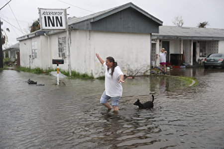 ROCKPORT, TX - AUGUST 26: Valerie Brown walks through a flooded area after leaving the apartment that she road out Hurricane Harvey in on August 26, 2017 in Rockport, Texas. Harvey made landfall shortly after 11 p.m. Friday, just north of Port Aransas as a Category 4 storm and is being reported as the strongest hurricane to hit the United States since Wilma in 2005. Forecasts call for as much as 30 inches of rain to fall in the next few days. (Photo by Joe Raedle/Getty Images)
