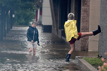 GALVESTON, TX - AUGUST 26: Residents walk along a street flooded by rain from Hurricane Harvey on August 26, 2017 in Galveston, Texas. Harvey, which made landfall north of Corpus Christi late last night, is expected to dump upwards to 40 inches of rain in Texas over the next couple of days. (Photo by Scott Olson/Getty Images)