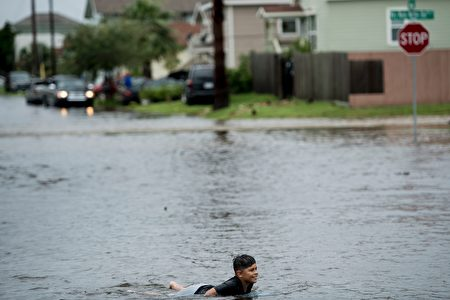 A boy plays in a flooded street as the effects of Hurricane Harvey are seen August 26, 2017 in Galveston, Texas. Hurricane Harvey left a trail of devastation Saturday after the most powerful storm to hit the US mainland in over a decade slammed into Texas, destroying homes, severing power supplies and forcing tens of thousands of residents to flee. / AFP PHOTO / Brendan Smialowski / The erroneous mention appearing in the metadata of this photo by Brendan Smialowski has been modified in AFP systems in the following manner: [Hurricane Harvey] instead of [Hurricane Henry]. Please immediately remove the erroneous mention from all your online services and delete it from your servers. If you have been authorized by AFP to distribute it to third parties, please ensure that the same actions are carried out by them. Failure to promptly comply with these instructions will entail liability on your part for any continued or post notification usage. Therefore we thank you very much for all your attention and prompt action. We are sorry for the inconvenience this notification may cause and remain at your disposal for any further information you may require. (Photo credit should read BRENDAN SMIALOWSKI/AFP/Getty Images)
