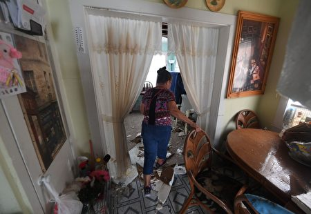 Celina Martinez returns to find her family home badly damaged after Hurricane Harvey hit Rockport, Texas on August 26, 2017. / AFP PHOTO / MARK RALSTON (Photo credit should read MARK RALSTON/AFP/Getty Images)