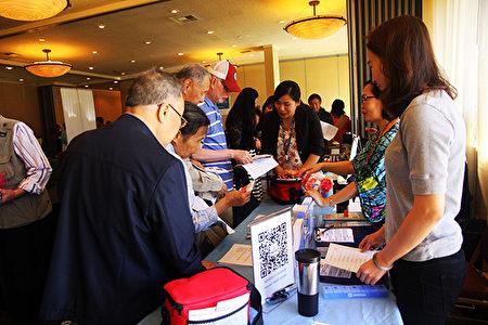 民众参观展商摊位了解和索取资讯。(Han Zhang/大纪元)