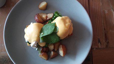 图:班尼迪克蛋(Egg Benny)是北美经典早午餐,店内有烤培根与黄油羽衣甘蓝两种可以选择。无麸质的司康饼软糯可口,呈现出密实蛋糕的口感与香气。搭配脆生的羽衣甘蓝,以及水煮蛋溏心与柠檬蛋黄酱,不仅口感丰富,而且具有饱腹感。(大纪元图片)