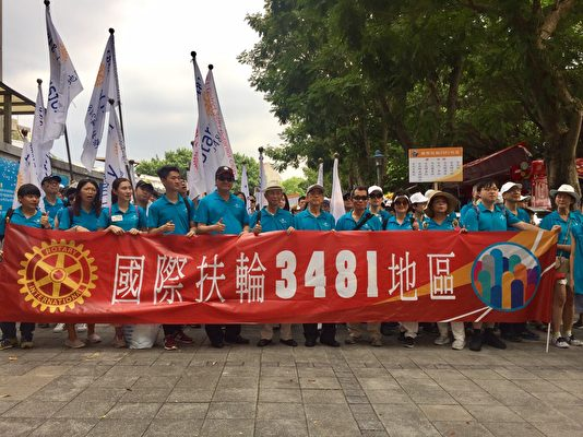 国际扶轮3481地区总监洪振攀(中),带领上百位扶轮社员参与世大运踩街游行。(扶轮社提供)