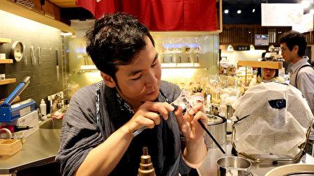 手塚真理正在制作金鱼糖艺。(树森/大纪元)