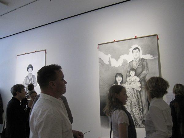 嘉賓在觀享遭中共迫害的法輪功學員的繪畫。(李樂/大紀元)