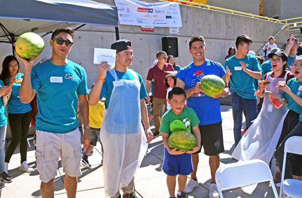 第五轮吃西瓜比赛的胜利者:中间举着白色信封的是第一名蔡键沣(Bruce),他右边的小朋友卡尔顿(Carlton)是第二名,两旁另2位站立抱西瓜者是并列第三名的参赛者。(黄剑宇/大纪元)