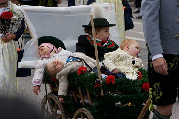 坐在小拉車上參加遊行的兒童睡得好香。(黃芩/大紀元)
