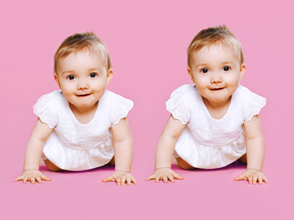 Portrait of two sweet twins baby crawls together。(fotolia)