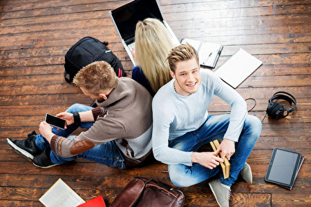 Group of students reading books, using a smartphone and notebook leaning on each other on wooden floor. (fotolia)