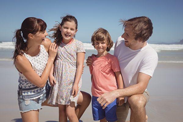 与父母在海滩愉快的兄弟姐妹