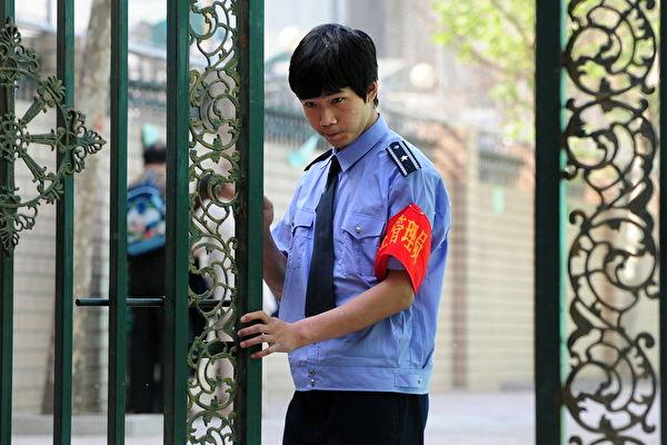 北京一所小学的保安人员在学生放学离开后关闭学校大门。(Frederic J. BROWN/AFP)