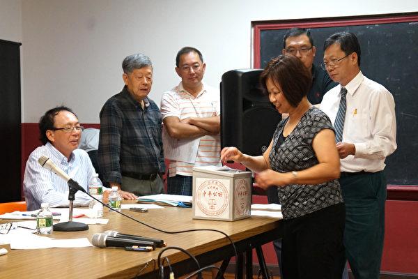 中华公所修改章程投票,财政李翠屏正投入票箱,选举小组成员们在一旁监票。(黄剑宇/大纪元)