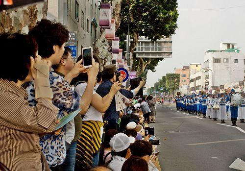 法轮功团体表演所到之处,都受到观众热情的鼓掌,观众们纷纷用手机拍照录像。(明慧网)