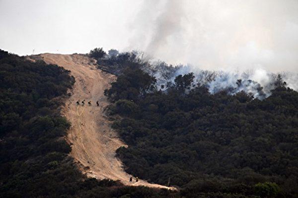 2017年9月2天,加利福尼亚州洛杉矶的消防队员在高峰架设水管灭火。山火造成8000公顷土地过火,连摧毁了三栋建筑居民吃强制撤离。眼看是洛杉矶市史上面积最大的山火。(AFP PHOTO / Robyn Beck)