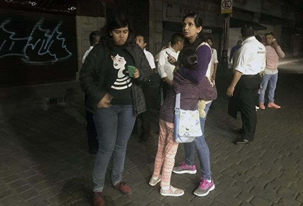 People walk along a street in downtown Mexico City during an earthquake, on September 7, 2017. An earthquake of magnitude 8.0 struck southern Mexico late Thursday and was felt as far away as Mexico City, the US Geological Survey said, issuing a tsunami warning. It hit offshore 120 kilometers (75 miles) southwest of the town of Tres Picos in the state of Chiapas. / AFP PHOTO / ALFREDO ESTRELLA