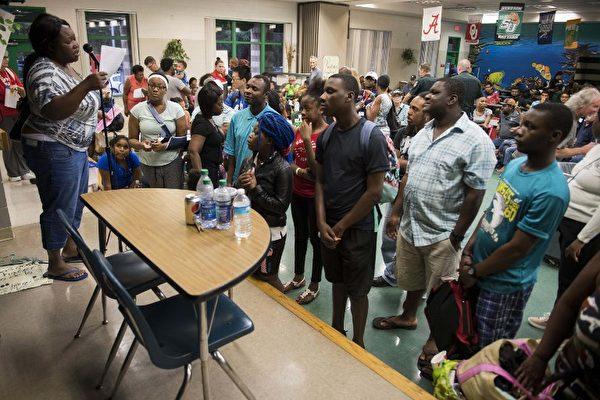 9月9日在佛羅里達州坦帕作為庇護所的一所小學裡,坦帕居民等待分發食物。 艾瑪颶風以最大強度5級颶風在古巴登陸後,9月9日略微減弱到4級風暴。(AFP PHOTO / JIM WATSON)