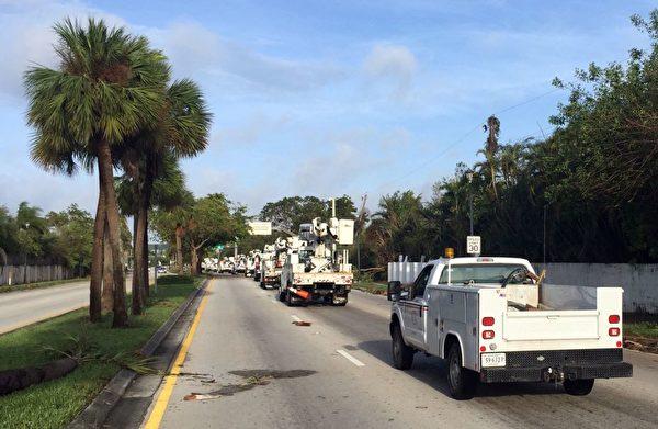 9月11日,电力公司卡车行驶在迈阿密。(MICHELE EVE SANDBERG/AFP/Getty Images)